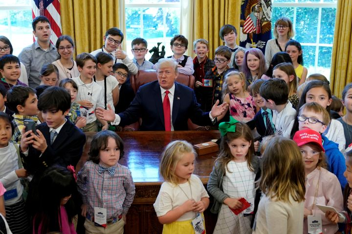 "U.S. President Donald Trump poses with children of staff and press in the Oval Office of the White House on ""take your child to work day"" in Washington. U.S., April 26, 2018. REUTERS/Kevin Lamarque"