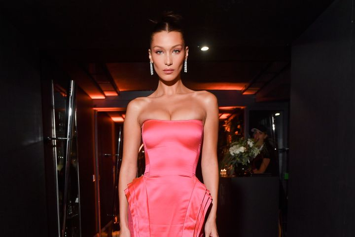 Bella Hadid wows in this pink, vintage Jean Paul Gaultier gown with a fitted silhouette and AS29 earrings in Paris.