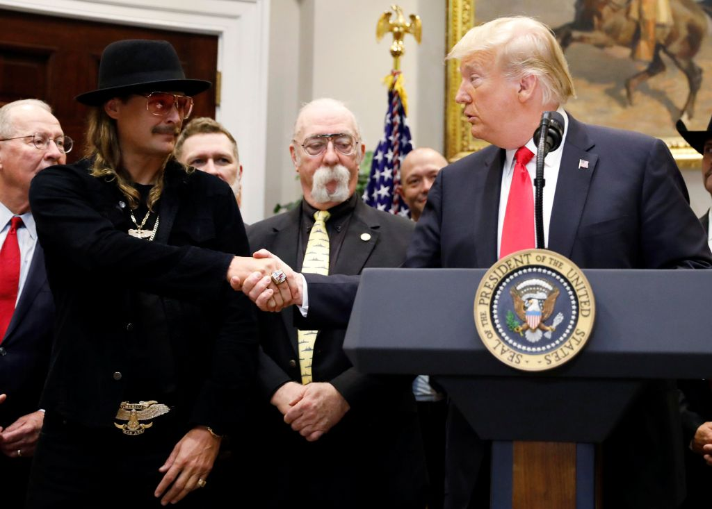 """U.S. President Donald Trump greets musician Kid Rock prior to signing the """"Orrin G. Hatch-Bob Goodlatte Music Modernization Act"""" in the Roosevelt Room at the White House in Washington, U.S., October 11, 2018."""