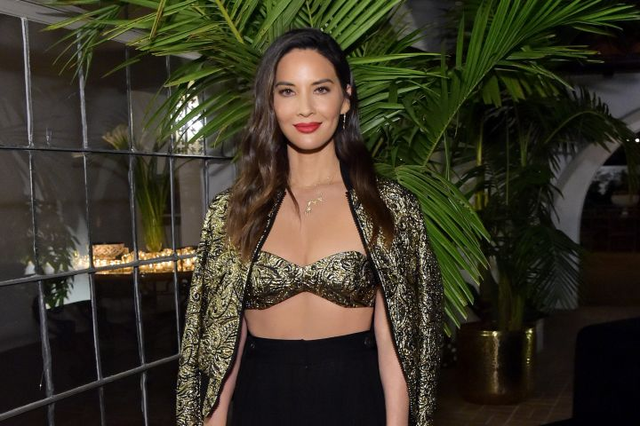 Olivia Munn shows some skin in a revealing outfit at the Michael Kors Dinner To Celebrate Kate Hudson. The 38-year-old actress wears a black and gold matching bra top and jacket paired with black flowy pants.
