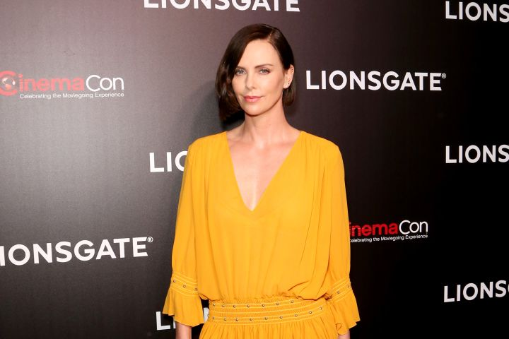 Charlize Theron shows off her playful side in this orange dress that complements her statuesque legs.