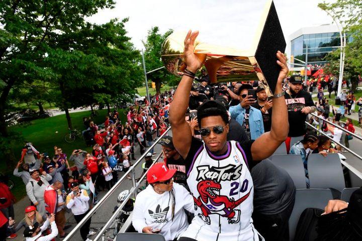 Toronto Raptors guard Kyle Lowry hoists the Larry O'Brien Championship Trophy during the 2019 Toronto Raptors Championship parade in Toronto on Monday, June 17, 2019.