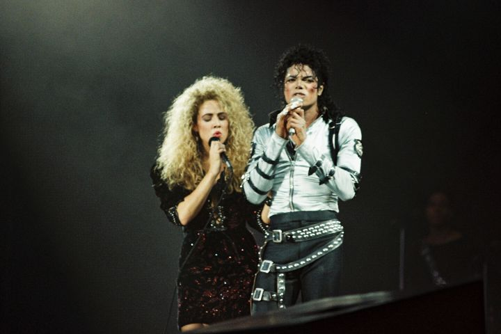 LONDON, UNITED KINGDOM - JULY 23: Sheryl Crow (L) joins Michael Jackson (R) to perform on stage on his BAD tour at Wembley Stadium on 23rd July 1988 in London, United Kingdom. (Photo by Pete Still/Redferns)