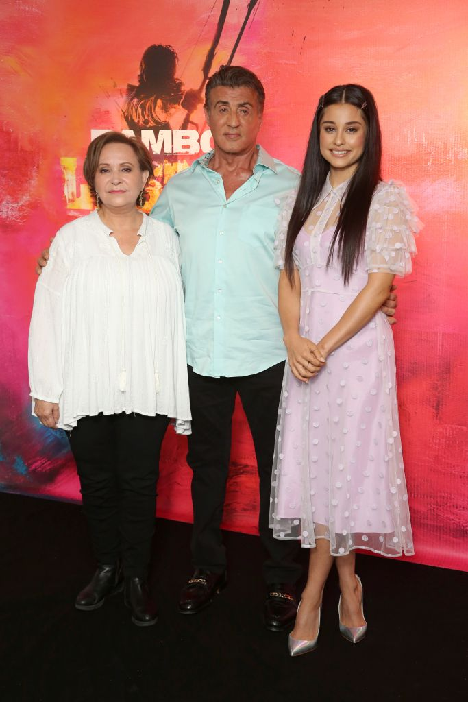 "Sylvester Stallone steps out in a light blue dress shirt and black pants to attend the L.A. photo call for ""Rambo: Last Blood"". The actor poses with his co-stars Adriana Barraza and Yvette Monreal. Barraza is wearing a white blouse and black trousers while Monreal dons a beautiful purple sheer dress and silver heels."