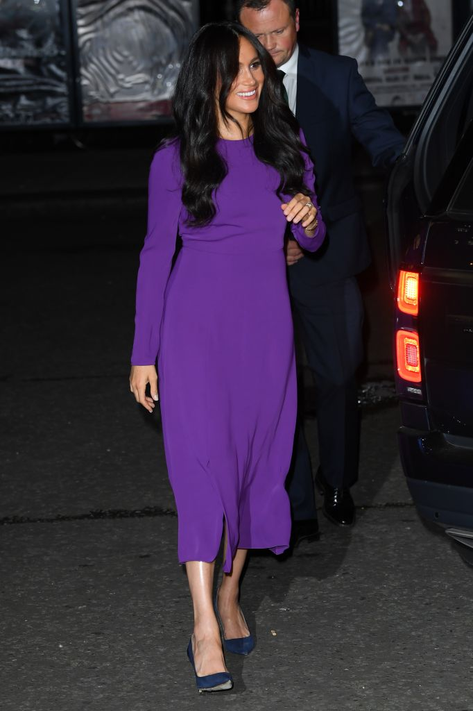 Just a couple of days after speaking out about being a mom in the media spotlight, Meghan Markle is all smiles as she arrives at the One Young World Summit opening ceremony in London. The Duchess of Sussex stuns in a recycled purple dress by Babaton – she previously wore the same midi dress while pregnant in January 2018 in Birkenhead – paired with navy suede heels. Photo: Shutterstock