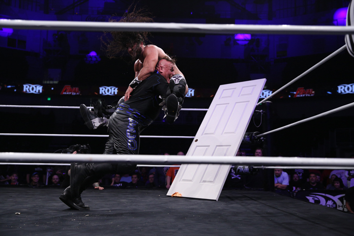 PCO slams Rush through a door frame at Final Battle. Courtesy: RING OF HONOR/ Zia Hiltey.