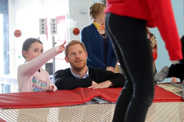Prince Harry speaks to participants as they watch a trampolining session during his visit to a Fit and Fed half-term initiative.