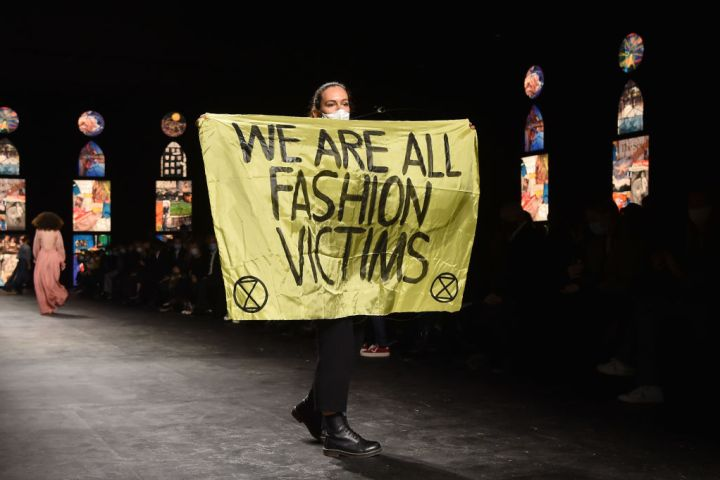 """PARIS, FRANCE - SEPTEMBER 29: A woman holds a banner which reads """"We are all fashion victims"""" as she walks on the runway during the Dior Womenswear Spring/Summer 2021 show as part of Paris Fashion Week on September 29, 2020 in Paris, France. (Photo by Stephane Cardinale - Corbis/Corbis via Getty Images)"""