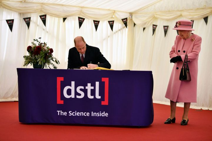 Britain's Queen Elizabeth II looks on as Prince William signs the visitors book during the visit to the Defence Science and Technology Laboratory (DSTL) at Porton Down, England, Thursday Oct. 15, 2020, to view the Energetics Enclosure and display of weaponry and tactics used in counter intelligence. (Ben Stansall/Pool via AP/CP Images)