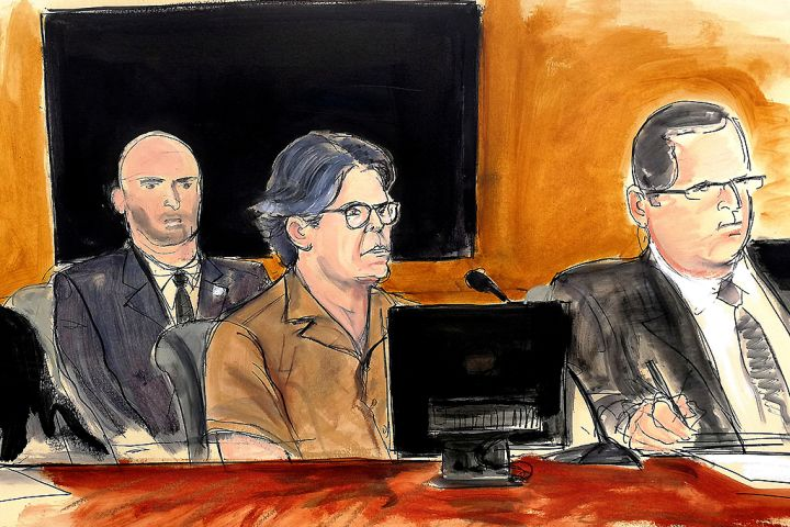 In this April 13, 2018 courtroom sketch, Keith Raniere, centre, leader of NXIVM, attends a hearing at court in New York.