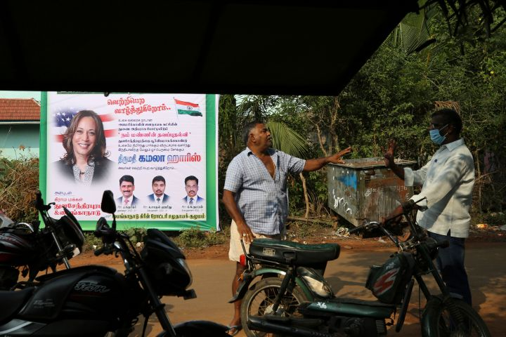 Two villagers interact next to a billboard wishing victory for U.S. democratic vice presidential candidate Sen. Kamala Harris in Thulasendrapuram village, south of Chennai, Tamil Nadu state, India, Tuesday, Nov. 3, 2020. The lush green village is the hometown of Harris' maternal grandfather who migrated from there decades ago. Photo: CP Images/AP Photo/Aijaz Rahi