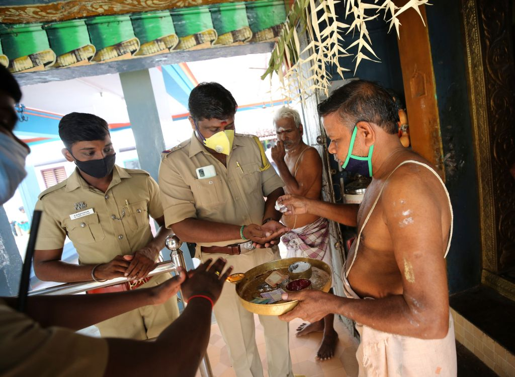 Indian police officials receive divine offerings from a Hindu priest after participating in a special prayer performed for the success of U.S. democratic vice presidential candidate Sen. Kamala Harris, at a temple in Thulasendrapuram village, south of Chennai, Tamil Nadu state, India, Tuesday, Nov. 3, 2020. Photo: CP Images/AP Photo/Aijaz Rahi