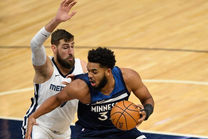 MINNEAPOLIS, MINNESOTA - JANUARY 13: Jonas Valanciunas #17 of the Memphis Grizzlies defends against Karl-Anthony Towns #32 of the Minnesota Timberwolves during the second quarter of the game at Target Center on January 13, 2021 in Minneapolis, Minnesota.