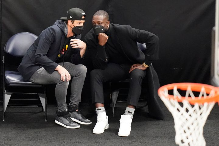Ryan Smith, left, and Dwyane Wade, right, speak in the first half during an NBA basketball game between the Indiana Pacers and Utah Jazz Friday, April 16, 2021, in Salt Lake City. Wade is an NBA owner. The Utah Jazz announced that the 13-time NBA All-Star will join the youngest ownership group in the league. The group is headed by technology entrepreneur Ryan Smith, who along with his wife, Ashley, acquired majority interest in the Jazz in late 2020.