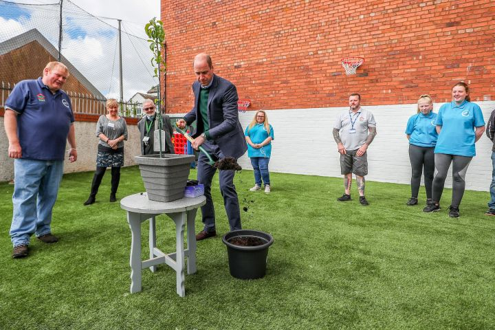 Prince William plants a tree in a pot during his visit to Brighter Futures, a consortium of eight local groups which encourage loal people to participate in community activities. Photo: PETER BYRNE/POOL/AFP via Getty Images