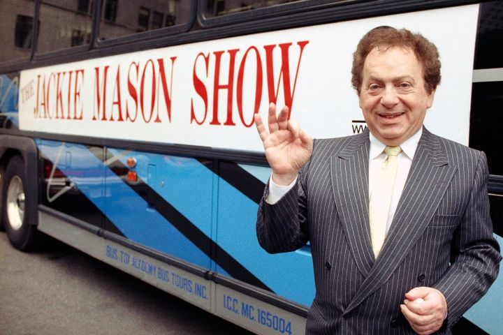 Jackie Mason stands beside a bus displaying a sign advertising his TV show, 1992.