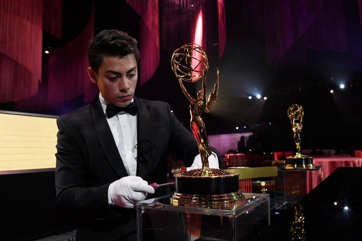 A worker removes a plaque from a Emmy Award statue in the engraving station during 71st Emmy Awards Governors Ball